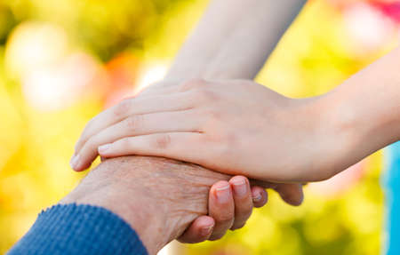 needy: Young hand holding an elderly man Stock Photo