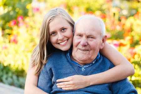 Prachtige kleindochter op bezoek bij haar bejaarde soort grootvader Stockfoto
