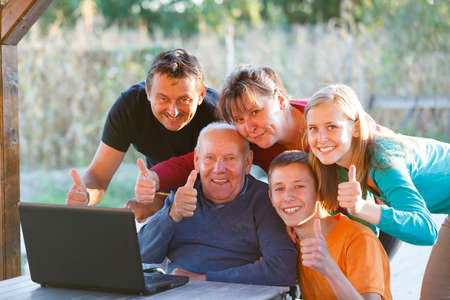 Happy family visiting grandfather, teaching him how to use the modern technology  Stock Photo