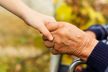 Young little boy shaking hands with old man