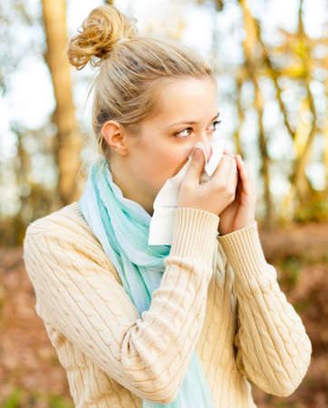Young beautiful women suffering from influenza, blowing her nose.
