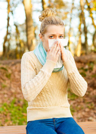 Young beautiful woman suffering from influenza, blowing her nose in handkerchief. Stock Photo