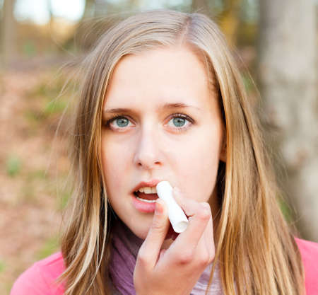dehydration: Young beautiful woman using lip balm to prevent dehydration during winter. Stock Photo