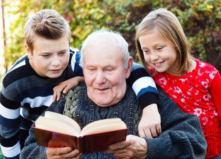 tell: Grandpa reading a beautiful fairy tale to his grandchildren.