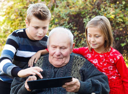 Curious grandfather learning from his grandchildren how to use a tablet.