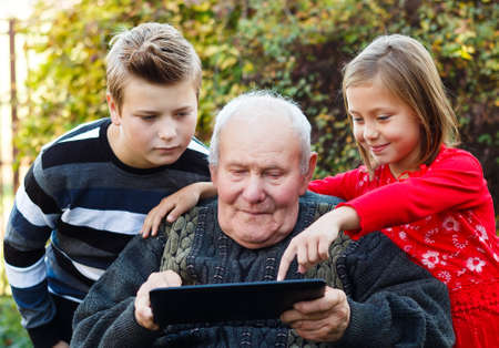 Beautiful granddaughter teaching grandfather to use a tablet.