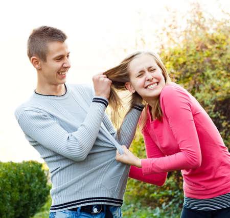 Siblings fighting, brother pulling his sisters hair.