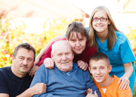 carer: Caring doctor together with her patients family. Stock Photo