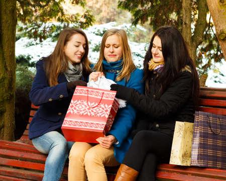 undoing: Young woment undoing their Christamas present.