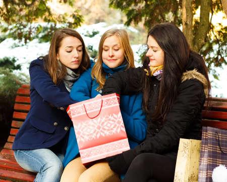 undoing: Curious women undoing their Chrsitmas present.