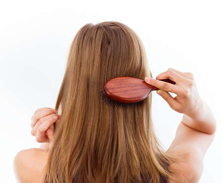 Woman combing her beautiful healthy hair.