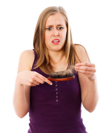 Young lady being shocked of the amount of her hair loss.