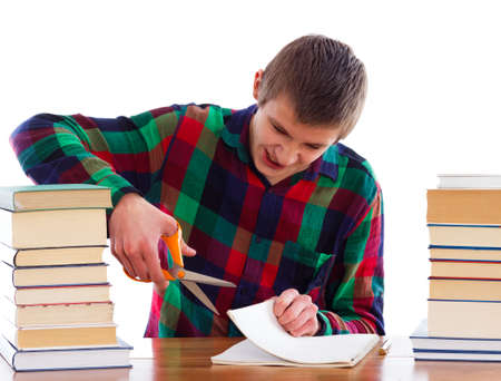 essay: Angry young student cutting his copybook. Stock Photo