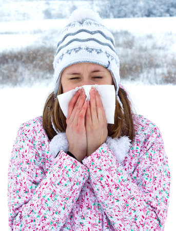 Winter sickness concept - woman blowing her nose. Stock Photo - 25514566