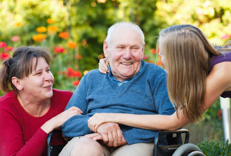 wheelchair man: Joyful family moment - loving grandfather with his beloved. Stock Photo