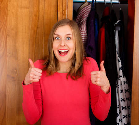 woman closet: Young excited woman showing thumbs up for her closet