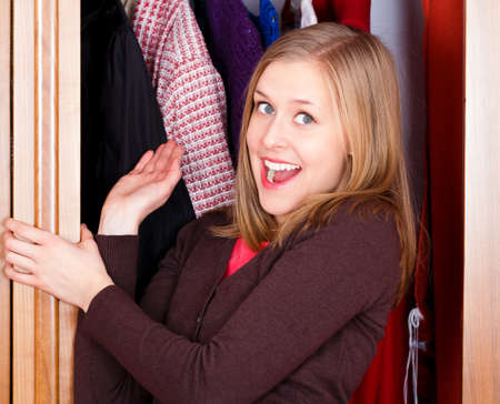 Shopaholic young lady with new clothes in her closet  photo