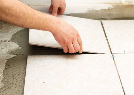 cemento: Handyman haciendo alicatado trabaja en cocina.