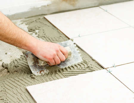 Bathroom floor tiling by manual worker. Stock Photo