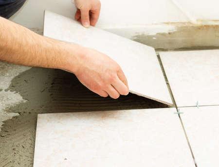 cerámicas: Trabajador manual que cubre piso del baño con azulejos caremic.