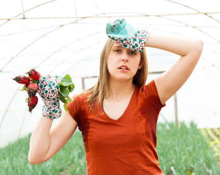 sweltering: Sweltering young gardener in hothouse after too much work. Stock Photo