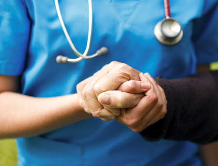 Doctor helping old patient with Alzheimer's disease.