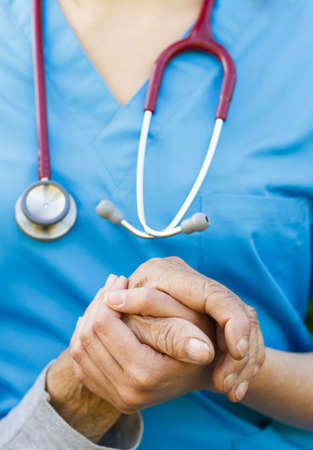 nursing aid: Close-up of and old hand being supported by a doctor. Stock Photo