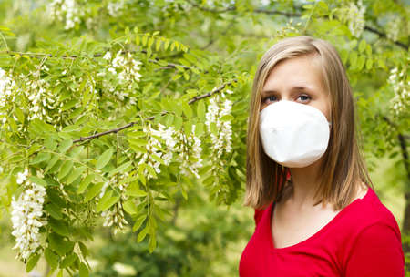 Young woman being allergic to wattle pollen, wearing mask.