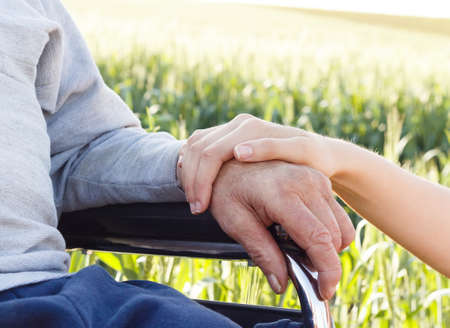 Supporting hand for grandfather with Alzheimer's disease. Standard-Bild