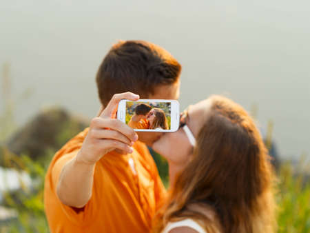 Taking a kissing selfie - teenage lovers in the sunset. photo