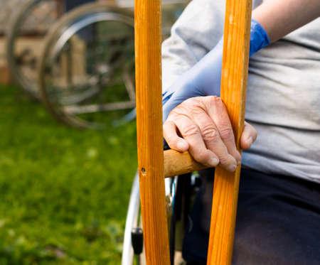homecare: Elderly homecare - nurse handing crutch to sick patient.