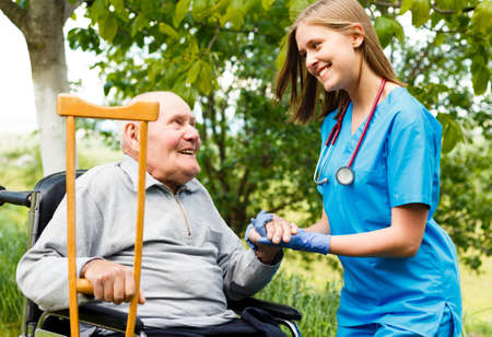 Contented senior patient with kind doctor at the nursing home. Stock Photo