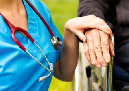 Professionele hulp voor ouderen in een rolstoel bij de verpleeghuizen. Stockfoto