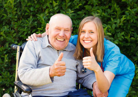 Happy smiling patient showing thumbs up together with his doctor. photo
