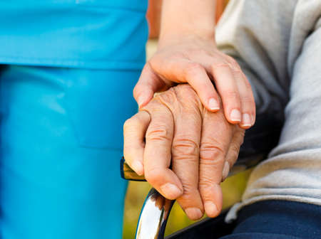 homecare: Conceptual image - support for the elderly in wheelchair. Stock Photo