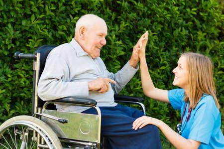 Médico juguetona con el paciente en el hogar de ancianos.