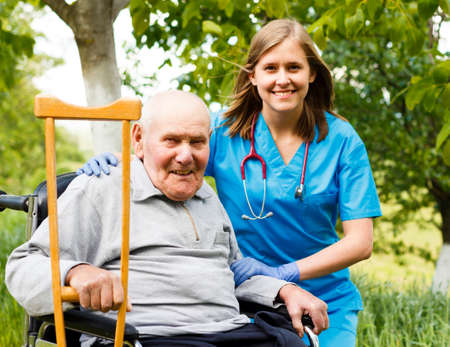 Happy old patient with supporting doctor at the nursing home. Standard-Bild