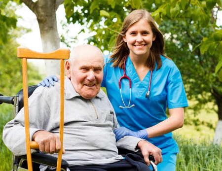 persona en silla de ruedas: Paciente mayor feliz con el apoyo médico en el hogar de ancianos.