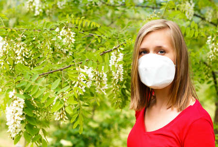 sensible: Young woman being allergic to wattle pollen, wearing mask.