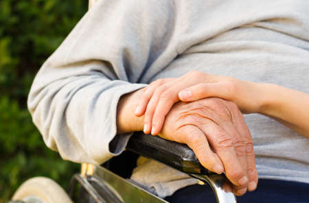 Supporting hand of a family member for old and disabled grandfather. Stock Photo