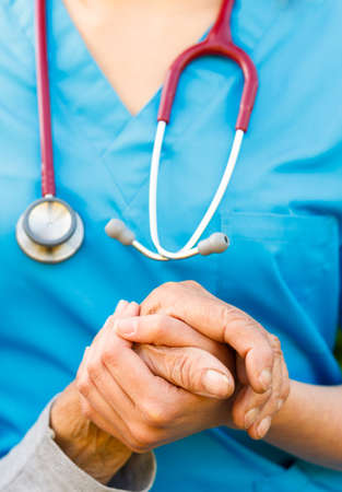 patient safety: Close-up of and old hand being supported by a doctor. Stock Photo