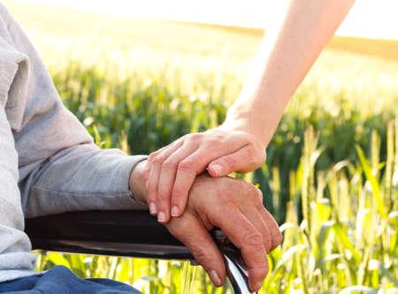 De zorg voor de ouderen in een rolstoel. Stockfoto