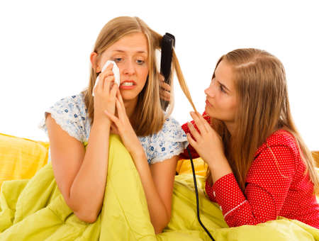 hangup: Supportive woman arranging girlfriends hair when she is feeling down. Stock Photo