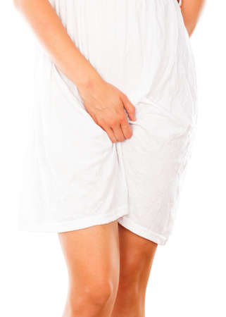 itchy: Conceptual image - woman in white dress showing signs of vaginal infection.