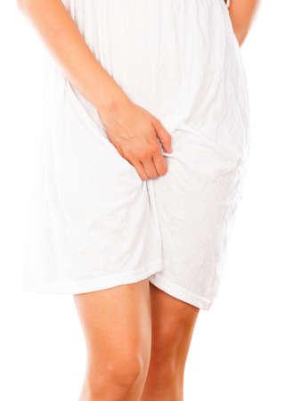 Conceptueel beeld - vrouw in witte jurk tekenen van vaginale infectie. Stockfoto