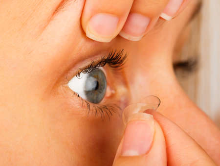 lentes contacto: Primer plano de mujer que quita sus lentes de contacto blandas.