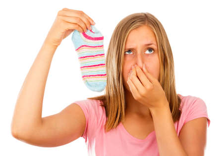 Funny image of young woman holding her breath near stinking socks. photo
