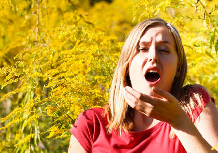 Young woman sneezing because of ragweed allergy.
