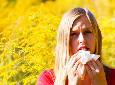 Snuffling young woman because of pollen allergy.