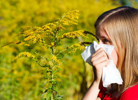 sensible: Young woman blowing nose in handkerchief because of allergy.